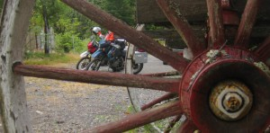 Motorcycles parked behind historical wheel
